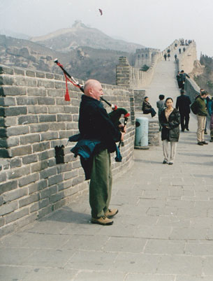 Jim blowing bag pipe on the Great Wall of china